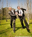 Two businessmen in a foot race through a park. The men are running in their business suits across green grass with leafless trees surrounding them.